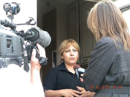 A woman is interviewed by a news crew